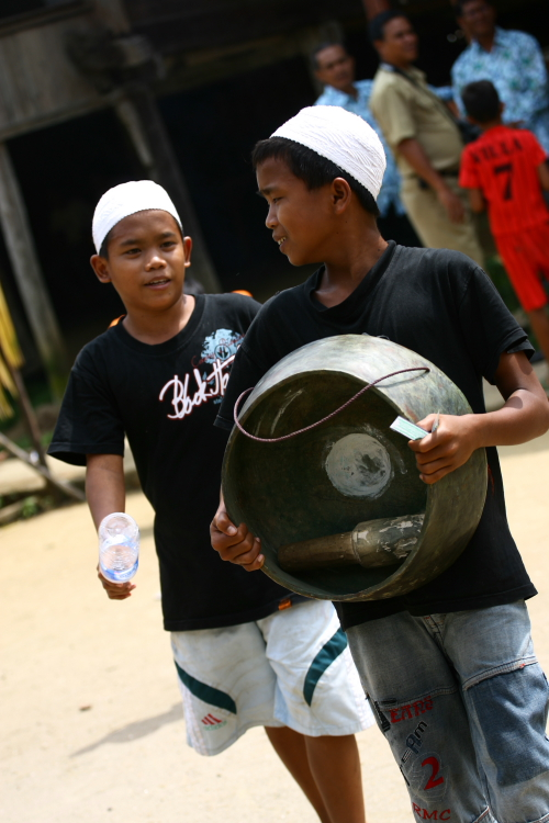 Boy Carrying a Gong in Front of Rumah Tuo