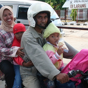 Family of four on a motorcycle. Only one helmet.