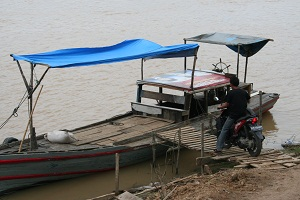 Our motorcycle being loaded onto the ketek (boat).