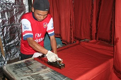 An employee applying a wax batik design to the already dyed cloth.