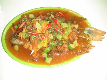 Fried fish smothered in sweet and sour sauce, and an assortment of chopped vegetables.
