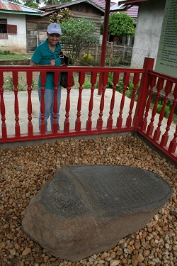 Phyllis, standing beside the fence around the engraved Karang Berahi stone.
