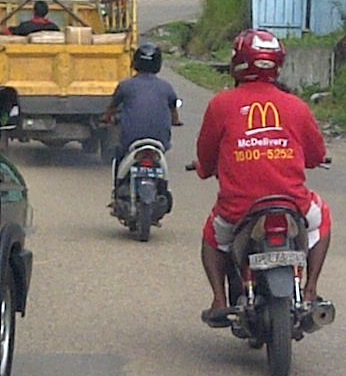 McDelivery This picture was taken in Jambi. The guy on the right is wearing a MacDonalds delivery advertisement. The jacket must have come from the City of Jakarta or Bandung because there are no MacDonald's restaurants in Jambi. Deliveries by MacDonalds & Pizza Hut in Indonesia are made with motorcycles.